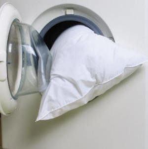 Coloque ambos na máquina de lavar, sem fronhas ou capas. Uma dica é colocar vinagre ao invés de amaciante